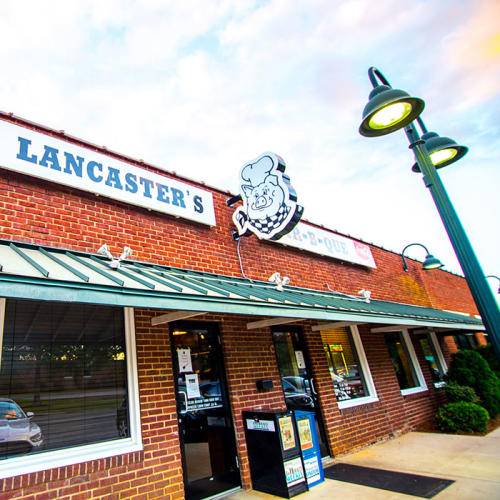 The sign over the entrance to Lancaster's features a pig in a chef's hat and checkered bandana.