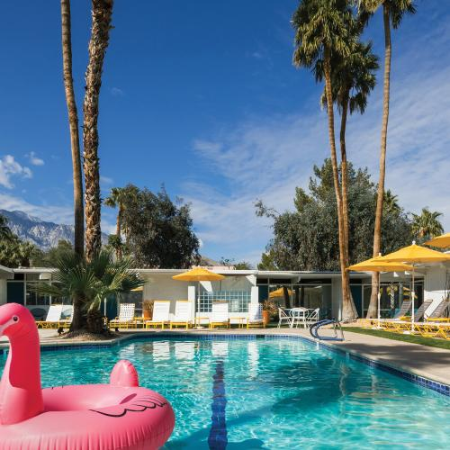 Photo of a pink flamingo pool float in a blue pool surrounded by yellow umbrellas and palm trees