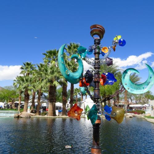 Wind sculpture displayed by lake.