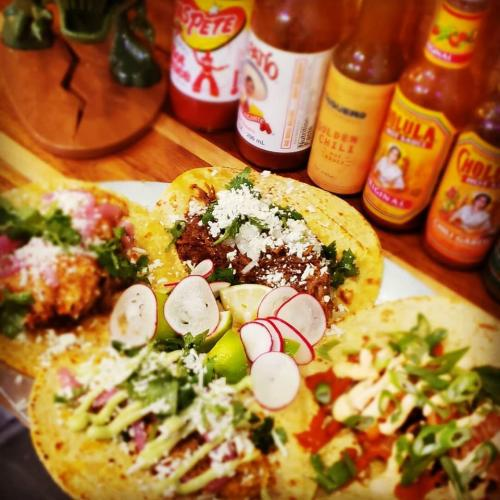 Taquero plate of tacos with row of sauces behind it