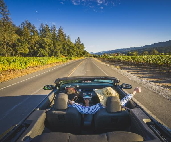 Visitors enjoy the sunshine and fresh air in their convertible on a drive through Napa Valley
