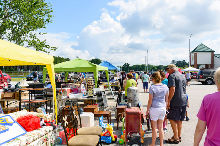 Shoppers stroll multiple vendor booths at a location along the 301 Endless Yard Sale
