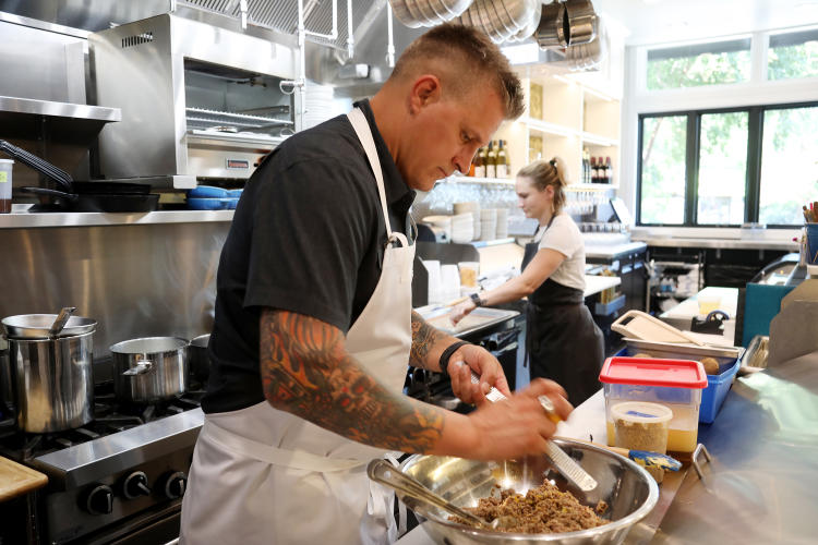 Chef Scott Crawford works to prepare a dish in the kitchen on one of his restaurants
