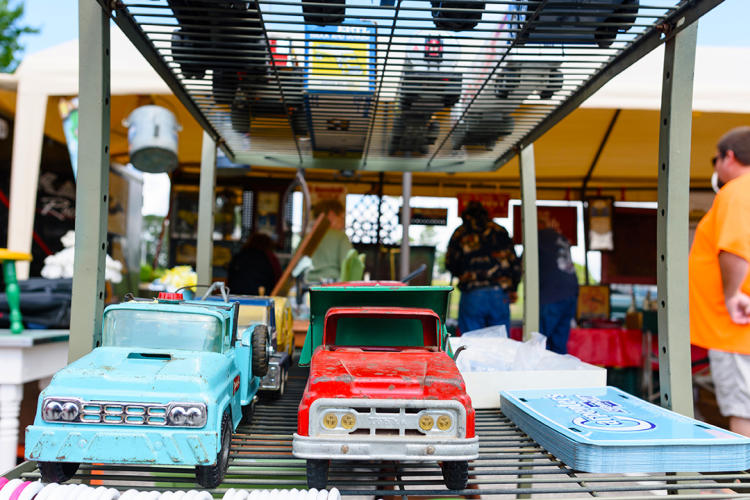 Toy trucks lined up for sale on a shelf at a yard sale