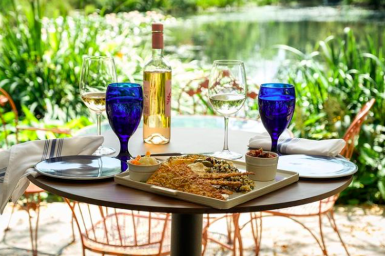 Beautiful Table set up with Blue water glasses and a bottle of white wine