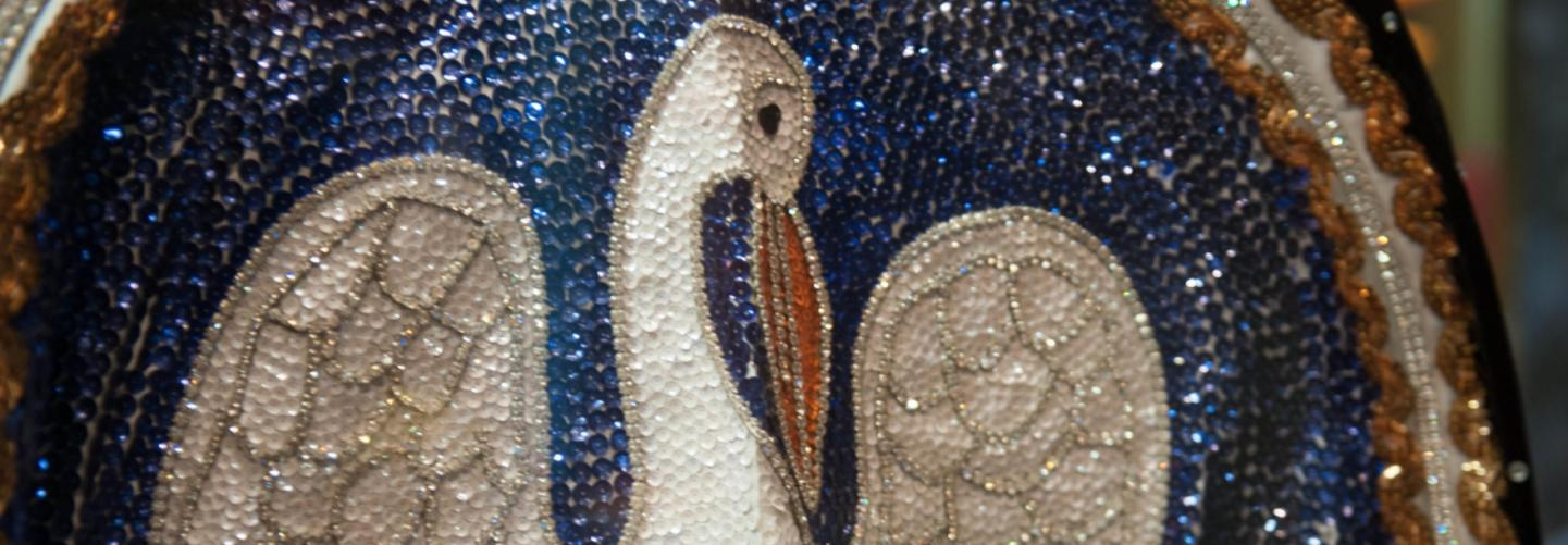 Close-up photo of beautiful sequin mosaic of white bird with two baby birds