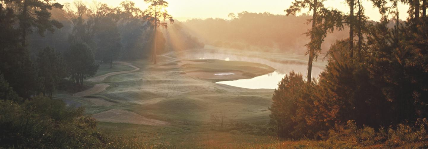 Sunlight filters in through the early morning mist over the green at The Bluffs Golf Resort, north of Baton Rouge.