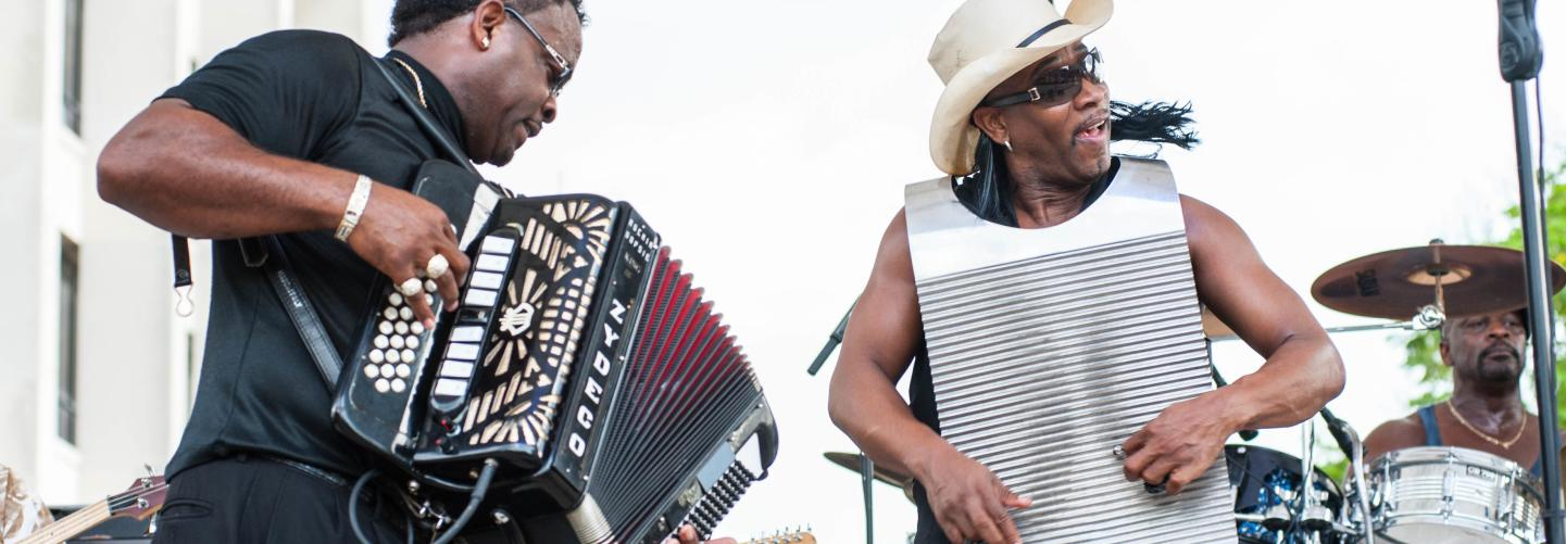 Accordion musician and singer performing on outdoor stage during festival