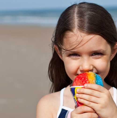 Girl eating snowcone on the beach