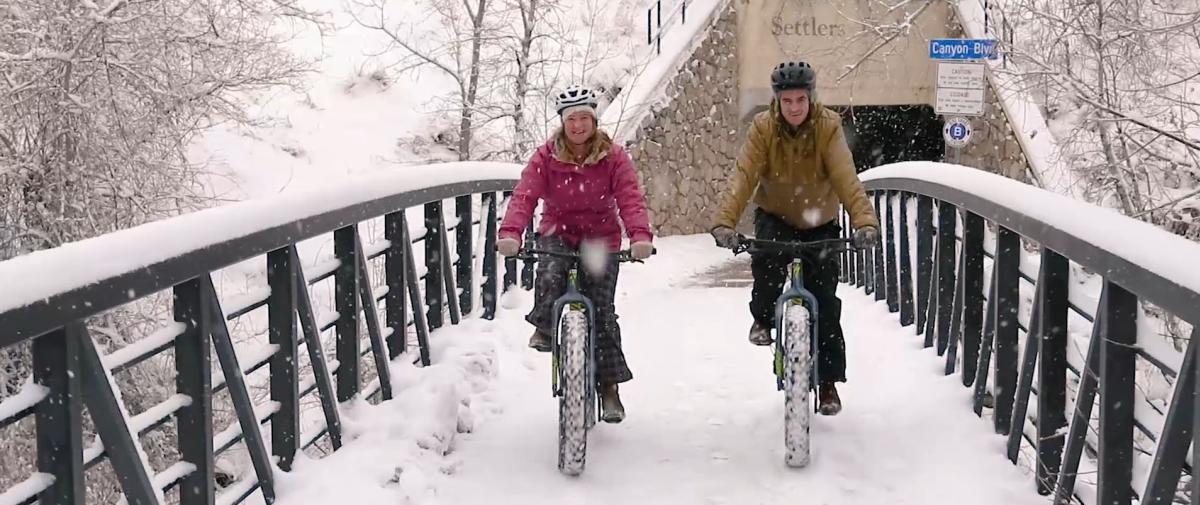 Couple riding fat tire bikes across bridge in Boulder