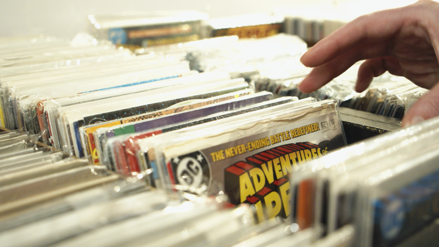 A person flips through old comic books at More Fun Comics & Games