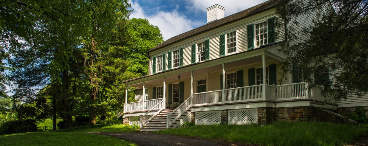 The exterior of John Jay Homestead State Historical Site on a sunny day with green foliage