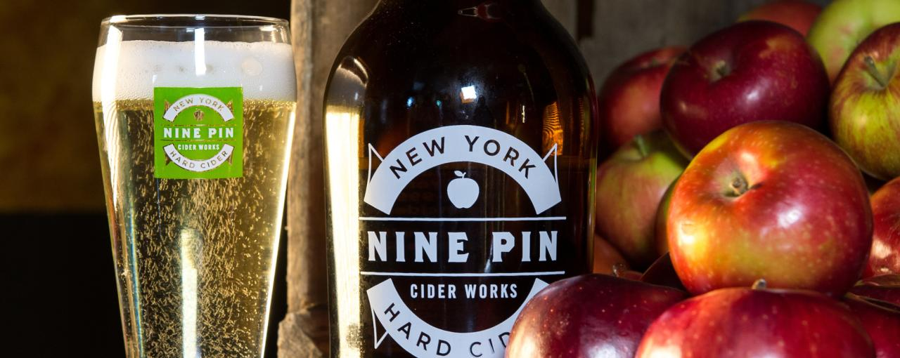 A photo of cider in a Nine Pin Cider Works glass