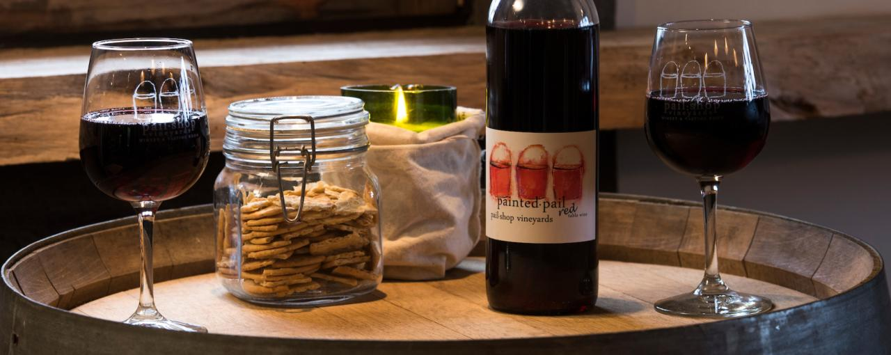 A photo of two wine glasses on a wooden board with a wine bottle and a jar of crackers