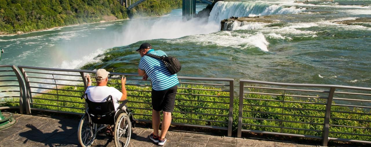 A man in a wheelchair and a companion look out at Niagara Falls