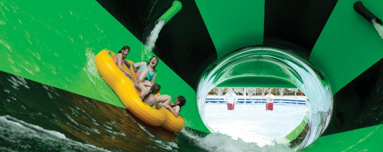 Four people ride the Alien Invasion water slide at Splish Splash Water Park
