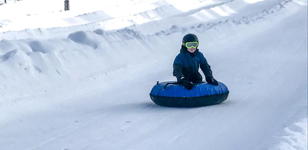 a boy rides a tube down a tubing lane