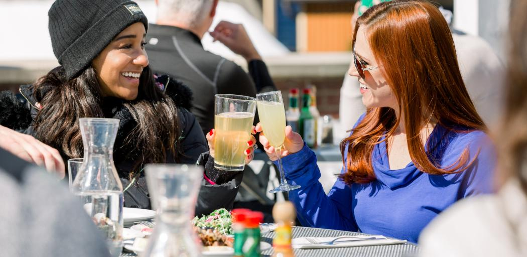 two girls cheers their drinks while outside
