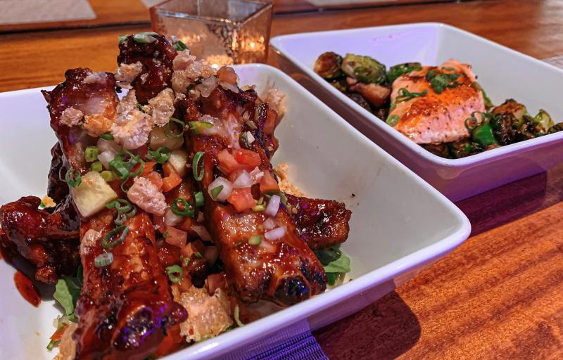 A rib dish and a salmon dish from Village Pub
