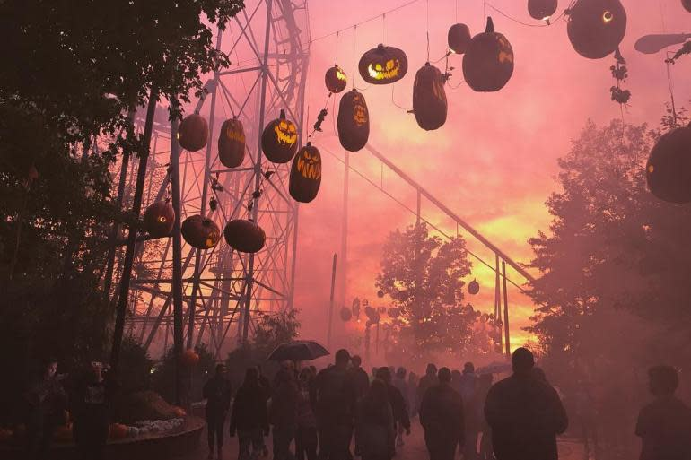 Jack o Lanterns hanging over a sidewalk full of people with a pink and yellow sky