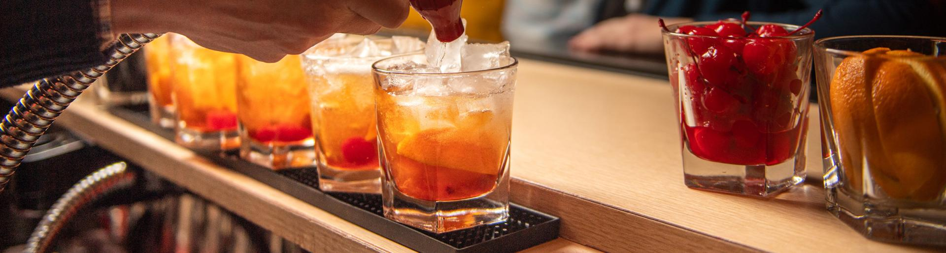 A bartender makes an Old Fashioned cocktail