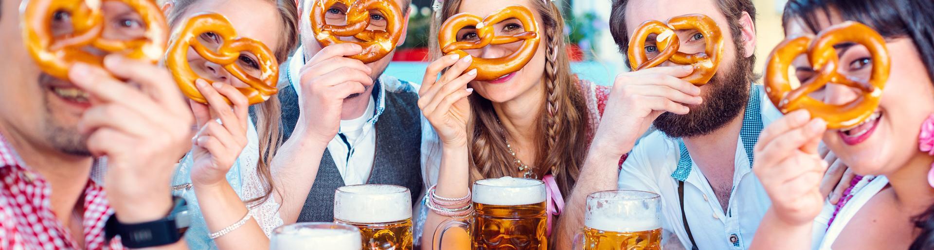 A group of friends at an Oktoberfest peer through the holes in a soft pretzel