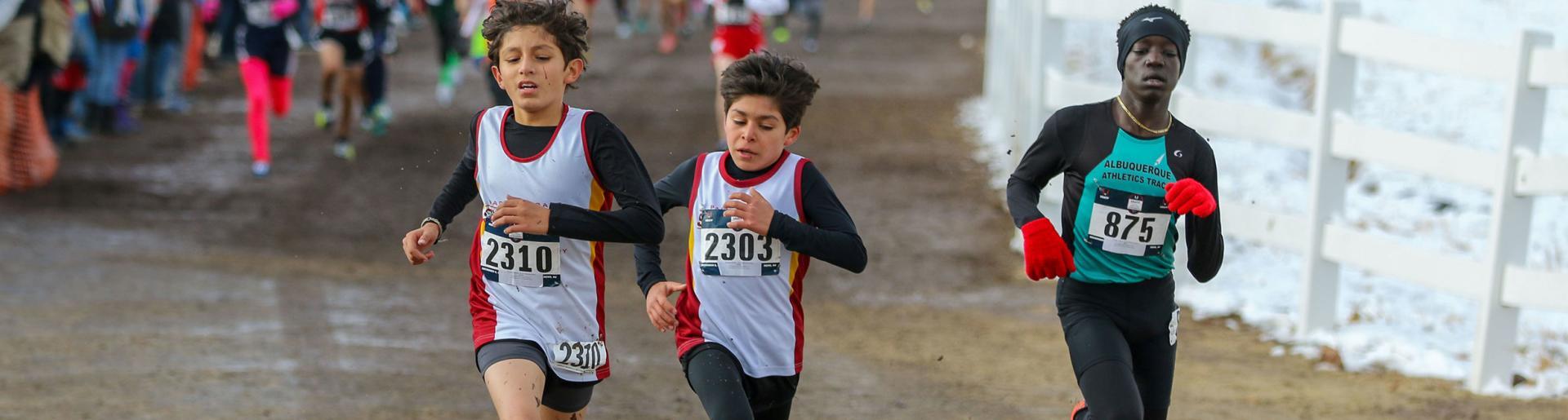 Three school-aged boys run uphill in cross country meet.