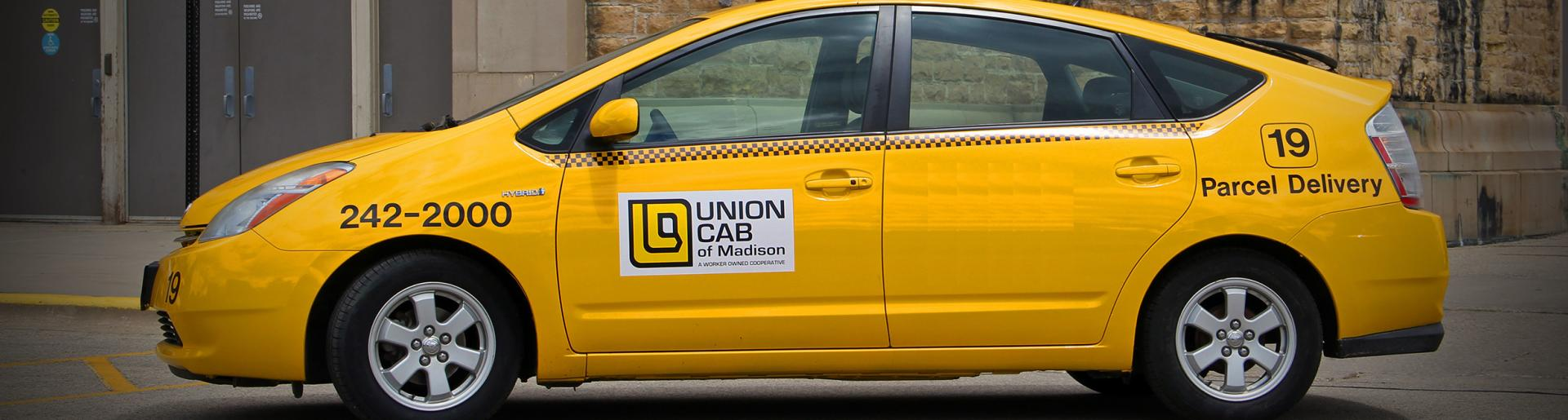 A Union Cab taxi parked in front of the Camp Randall Fieldhouse