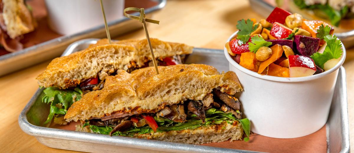 A sandwich on a tray with a fruit cup - a lunch option at Under the Oak