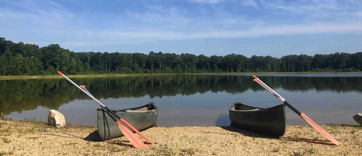 Two canoes sit on the sandy edge of a large lake at Howell Woods