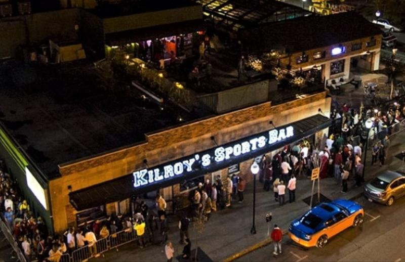 Kilroy's Sports Bar at night with people lined up around the building