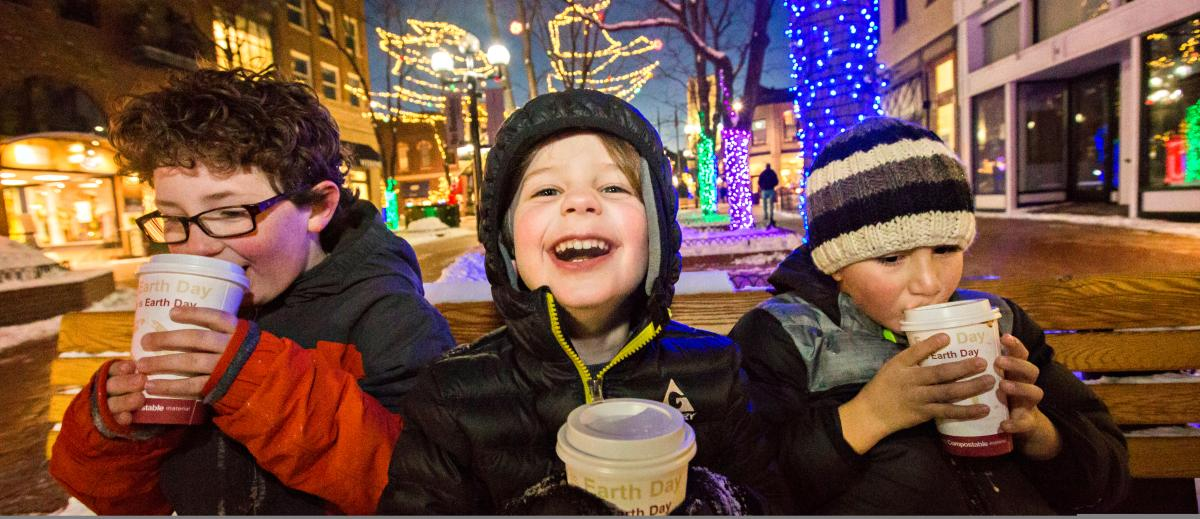Kids sitting on a  Pearl Street bench drinking hot chocolate