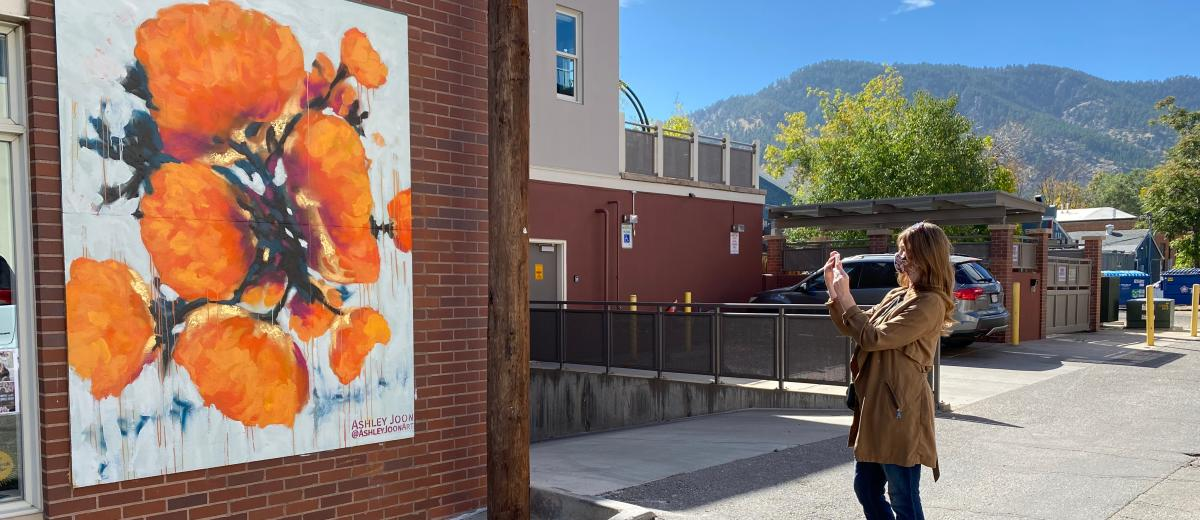 A visitor snaps a quick picture of this bright Ashley Joon Mural in Boulder.