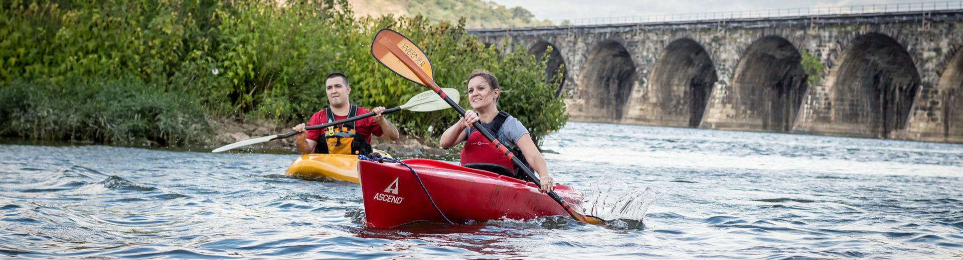 Couple kayaking in Hershey river with bridge