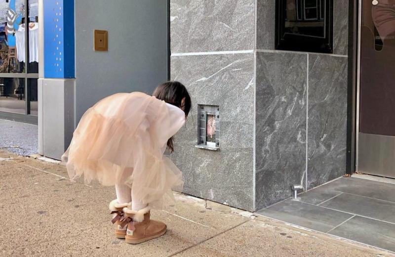 Girl looking at fairy doors in Ann Arbor