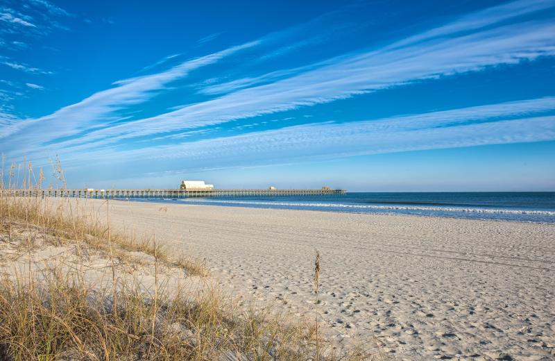a long pier stretches into the ocean from an empty, sandy beach in North Myrtle Beach, SC