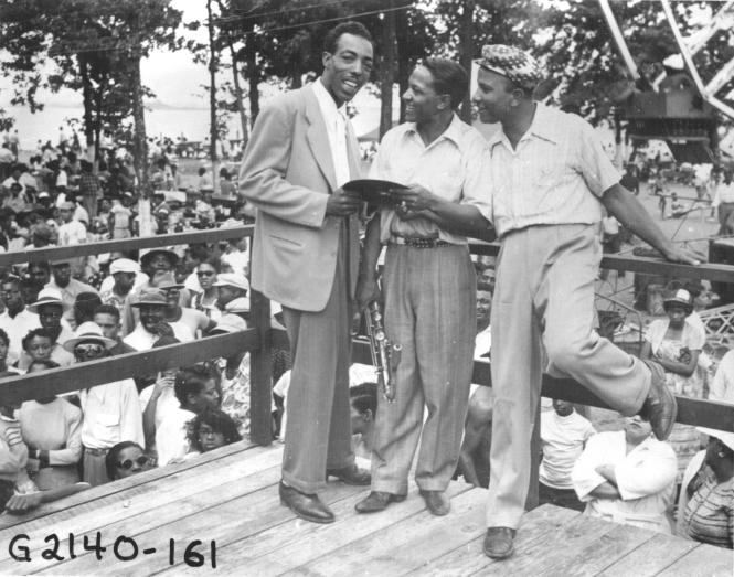 Carr's Beach, Hoppy Adams and two men stand on the grandstand.