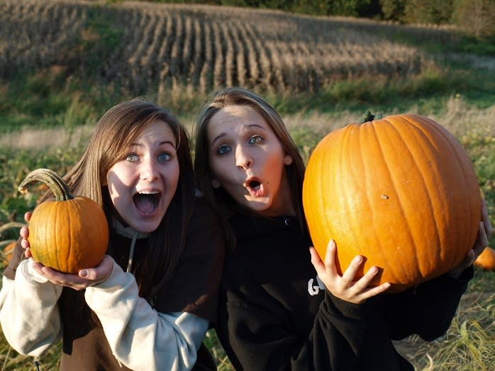 Two young women smile and hold up their pumpkins for the camera