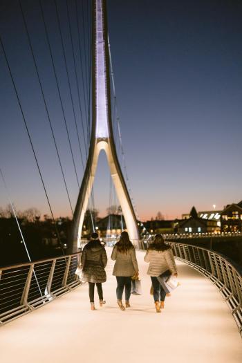 Three girls walking on the Dublin Link pedestrian bridge at night