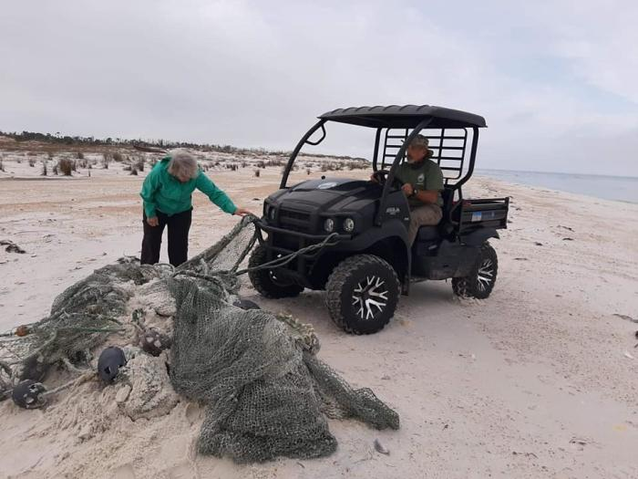 Volunteers at a beach clean-up event help to remove netting from the beach. Photo credit:Penny Weining