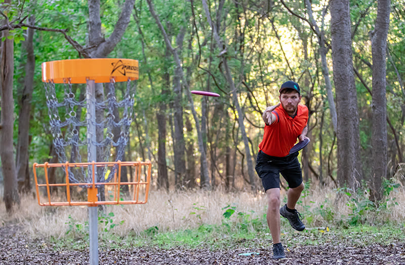 Man wearing a red shirt and black shorts tosses a frisbee towards an orange disc golf basket for the National Amateur Disc Golf Tour