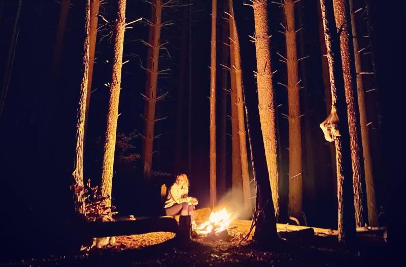Woman sitting by a bonfire in the Hoosier National Forest