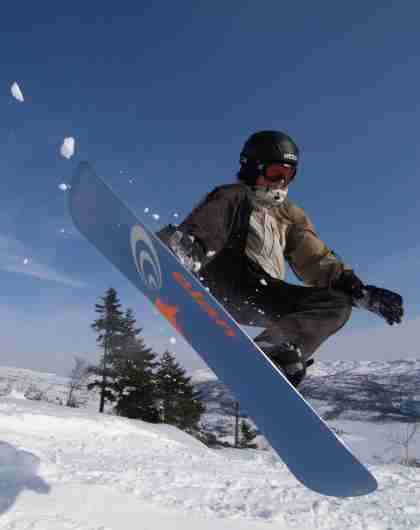 Boy dooing a jump on his snowboard
