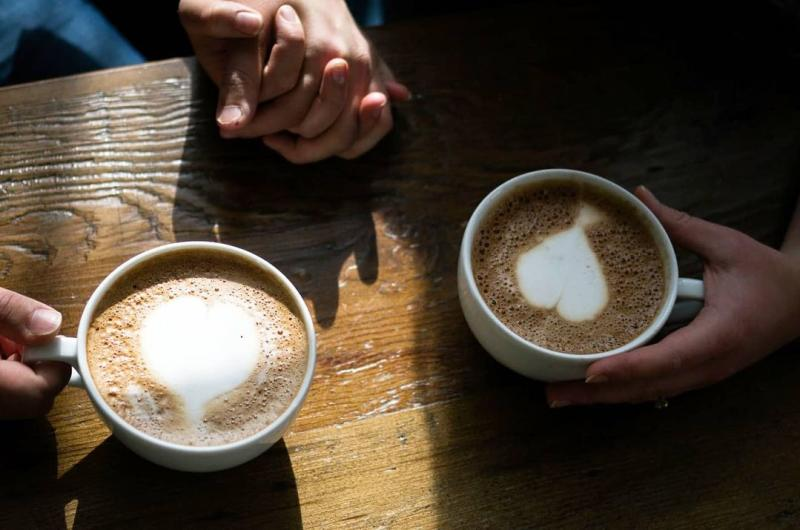 Two people holding hands and lattes