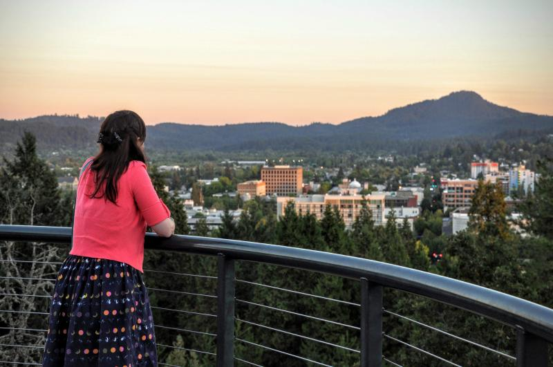 A woman stands at railing overlooking the city of Eugene with Spencer Butte in the background.
