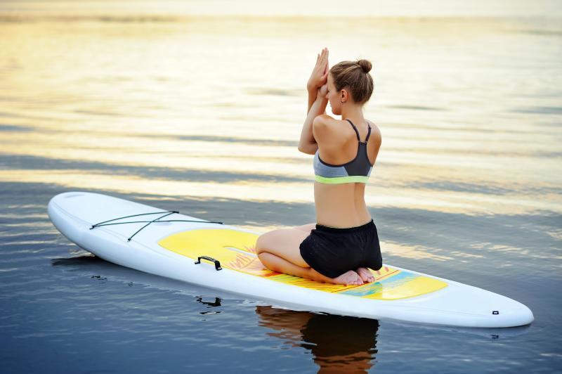 A yogi practices a modified Eagle Pose while sitting on a stand-up paddleboard.