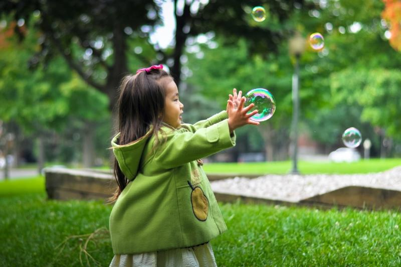 Small child chases bubbles in a park