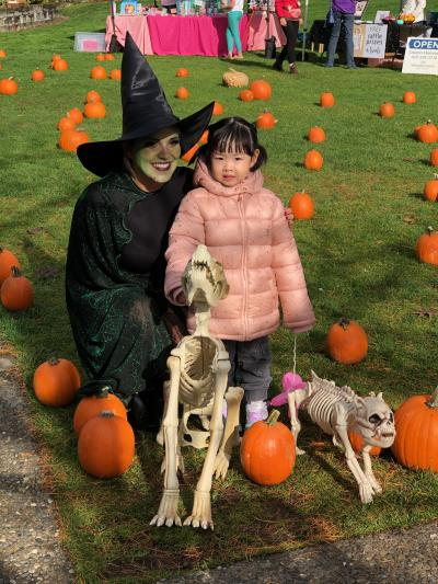KDA event manager in witch costume with young kid