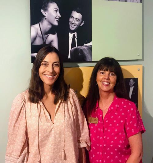Cecilia Peck standing next to Lynell Seabold at the Ava Gardner Museum in front of a photo of Ava Gardner and Gregory Peck