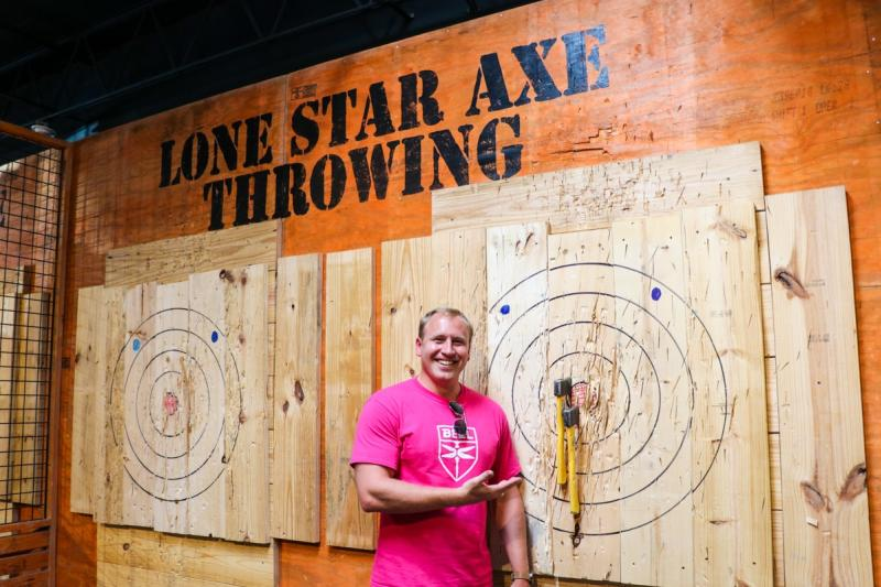 Photo of person next to axe on a bullseye at Lone Star Axe Throwing